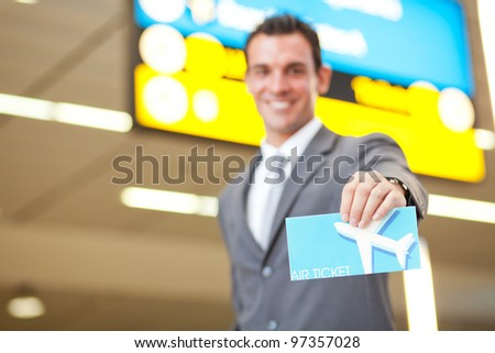 happy young businessman presenting air ticket, focus on foreground