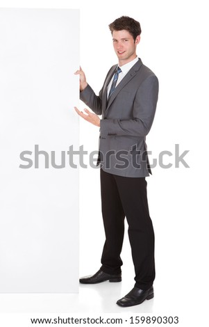 Happy Young Businessman Presenting Blank Placard Over White Background