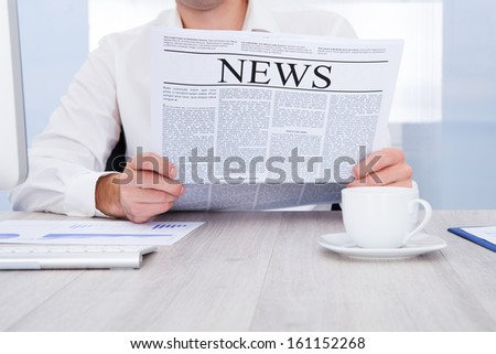 Happy Young Businessman Reading Newspaper At Office Desk - stock photo