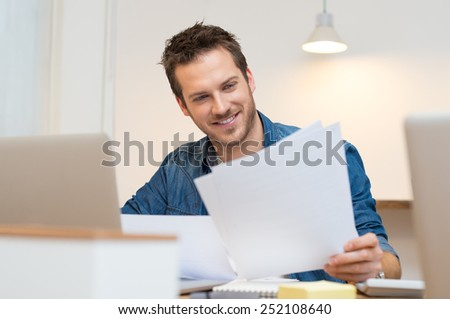 Happy young businessman reading paperwork at desk in office   - stock photo