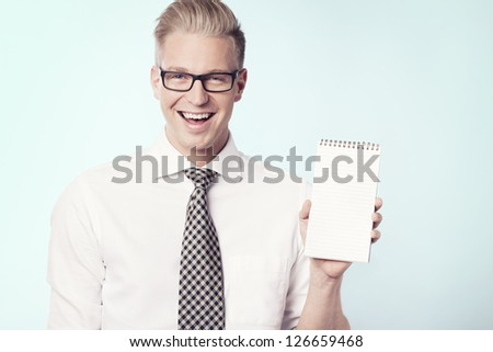 Happy young businessman showing empty notebook with space for text, isolated. - stock photo