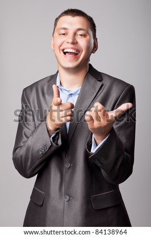 happy young businessman shows forefingers - stock photo
