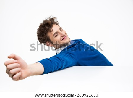 Happy young businessman sitting at the table and stretching - stock photo