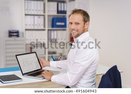 Happy young businessman sitting in the office working on a spreadsheet on his laptop computer turning in his chair to smile at the camera