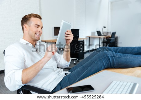 Happy young businessman sitting with legs on table and using tablet at workplace - stock photo