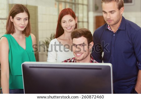 Happy young businessman smiling at his success as he sits working at a large screen desktop computer watched by a group of colleagues standing behind him - stock photo