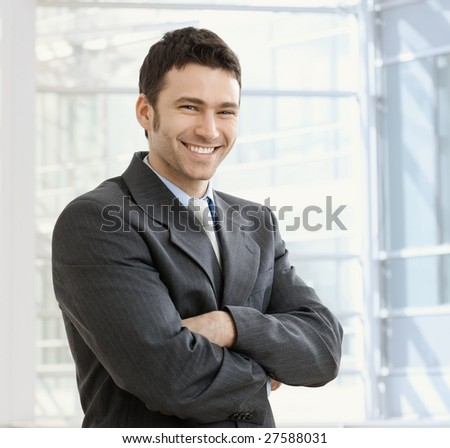Happy young businessman smiling at office. - stock photo