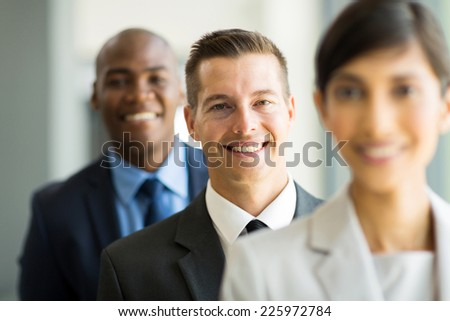 happy young businessman standing in a row with colleagues - stock photo