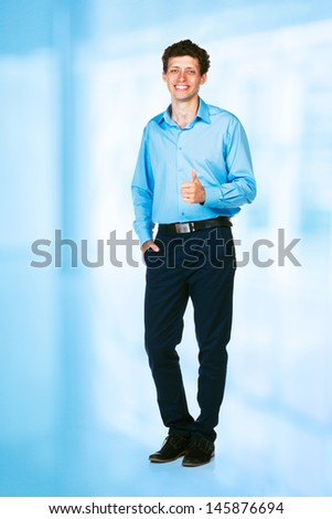Happy young businessman standing with thumb up in his office - stock photo