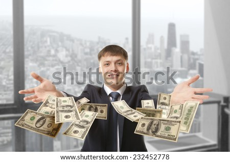 Happy young businessman throwing dollar