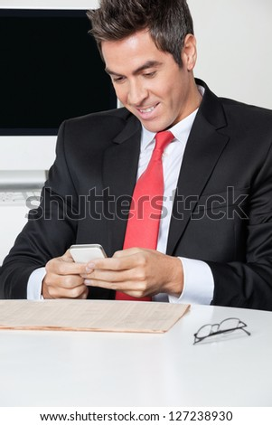 Happy young businessman using cell phone at desk in office - stock photo