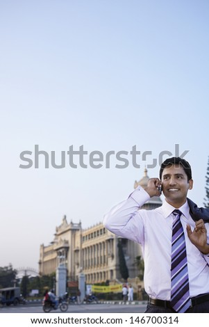 Happy young businessman using cell phone on city street - stock photo