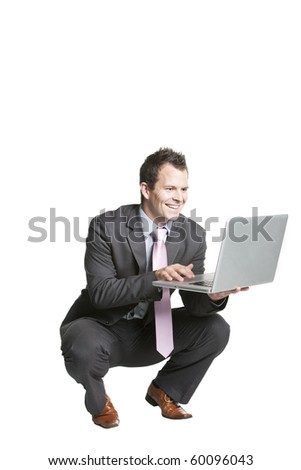 Happy young businessman using laptop - stock photo