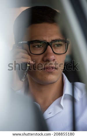 Happy young businessman using mobile phone in back seat of car - stock photo