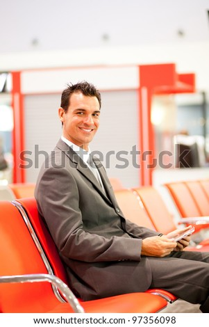 happy young businessman using tablet at airport - stock photo