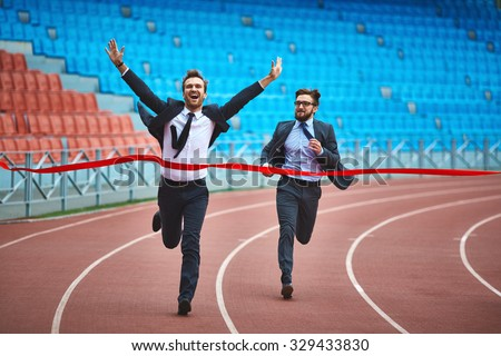 Happy young businessman winning the race - stock photo