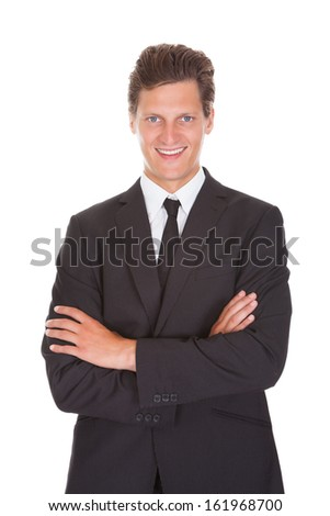 Happy Young Businessman With Arm Crossed Standing On White Background