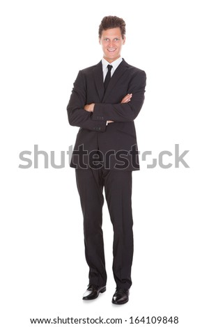 Happy Young Businessman With Arm Crossed Standing On White Background - stock photo