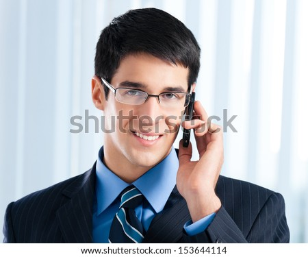 Happy young businessman with cell phone, at office