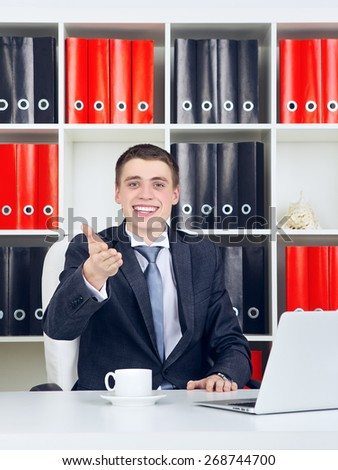 happy young businessman with laptop in his office - stock photo