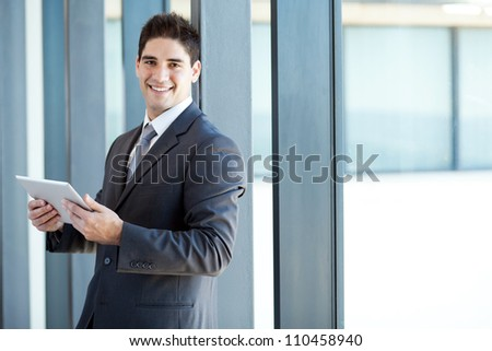 happy young businessman with tablet computer in office