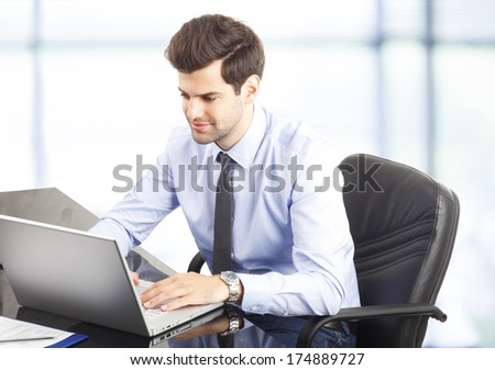Happy young businessman working on laptop in his office.