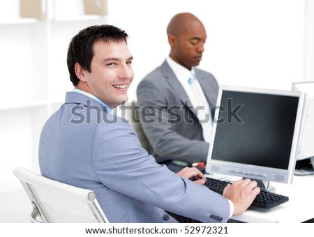 Happy young businessmen working at computers in the office - stock photo