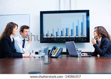 Happy young businesspeople having meeting in boardroom at office in front of a huge plasma TV screen, indoor, smiling. - stock photo