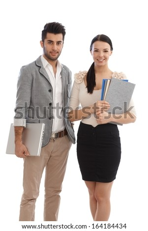 Happy young businesspeople holding files and laptop. - stock photo