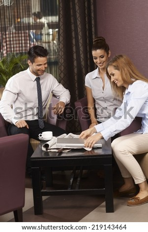 Happy young businesspeople working together in bar. - stock photo