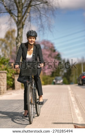 Happy Young Businesswoman Biking at the Street with Head Gear Going to her Office, Looking at the Camera - stock photo