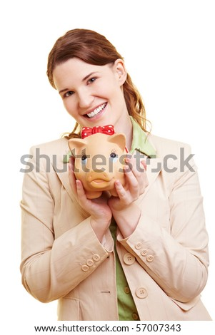 Happy young businesswoman carrying a piggy bank - stock photo
