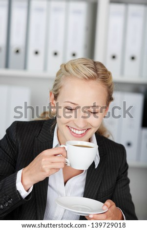 Happy young businesswoman drinking coffee in office - stock photo