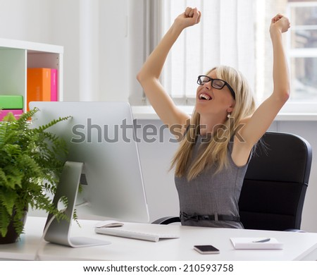 Happy young businesswoman enjoying success at work