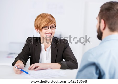 Happy young businesswoman explaining document to male coworker at office desk - stock photo