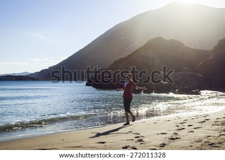 Happy young businesswoman going down seashore - stock photo