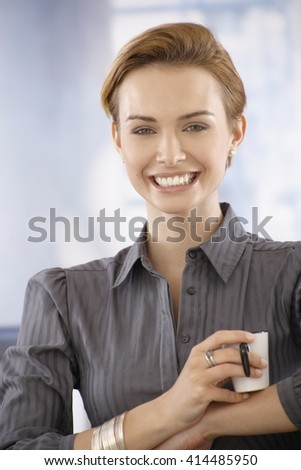 Happy young businesswoman having coffee-break, looking at camera. - stock photo