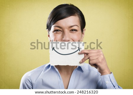 Happy young businesswoman holding blank white card with space for text in front of her mouth, isolated on yellow background. - stock photo