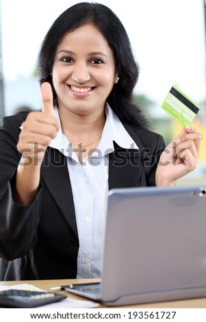 Happy young businesswoman holding credit card and showing thumbs up gesture