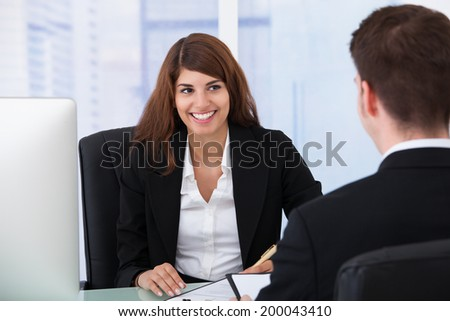 Happy young businesswoman interviewing male candidate at desk in office - stock photo