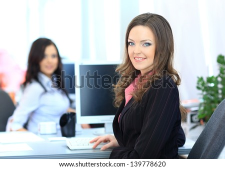 Happy young businesswoman looking behind and her colleagues working at office