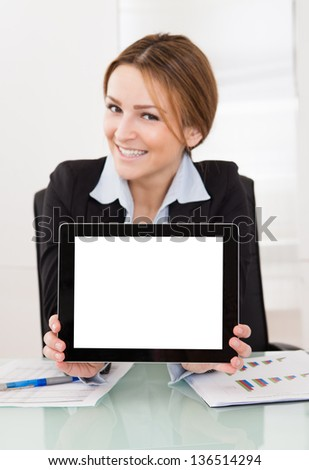 Happy Young Businesswoman Presenting Digital Tablet In The Office - stock photo