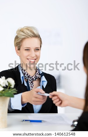 Happy young businesswoman receiving cardkey from receptionist at reception - stock photo
