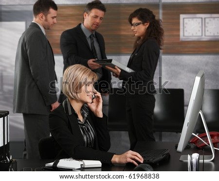 Happy young businesswoman sitting at office desk calling smiling.? - stock photo