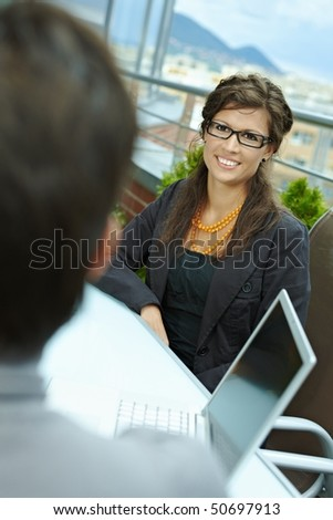 Happy young businesswoman sitting outdoor on office terrace and talking, smiling. Over the shoulder view. - stock photo
