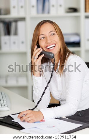 Happy young businesswoman using land line phone at office desk - stock photo