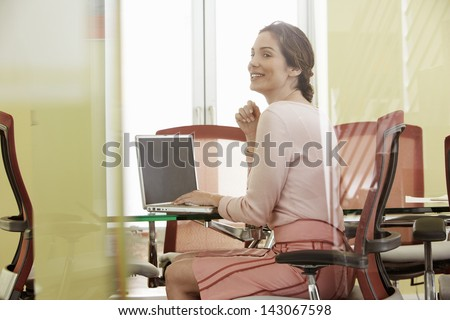 Happy young businesswoman using laptop in meeting room - stock photo