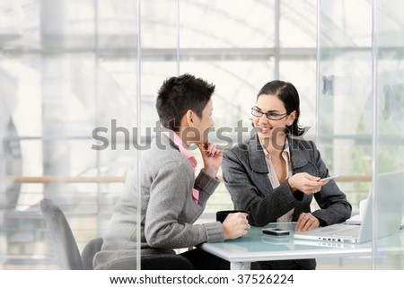 Happy young businesswomen having a meeting. Sitting at desk, looking at each other, smiling. - stock photo