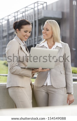 Happy young businesswomen with laptop standing against office building
