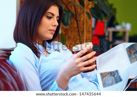 Happy young busineswoman sitting in the office with laptop and coffee - stock photo